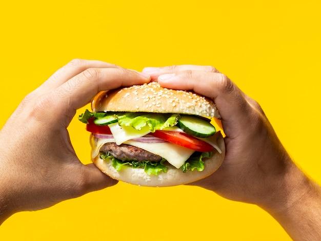 Hände, die cheeseburger mit samen halten