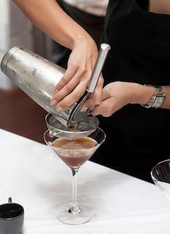 Hände, die cocktail gießen
