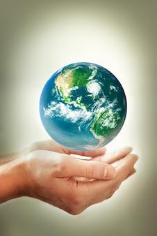 Hände, die das erdkonzept des erdtages halten, das energie spart, um das umweltelement zu schützen ...