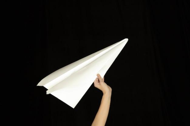 Hände, die das zeichen des papierfliegers oder der nachricht auf schwarzem hintergrund halten