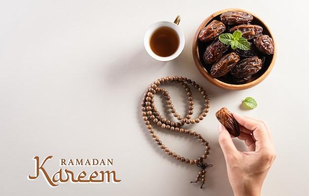 Hände, die dattelnfruchtee und rosenkranzperlen mit ramadan-kareem-text aufheben