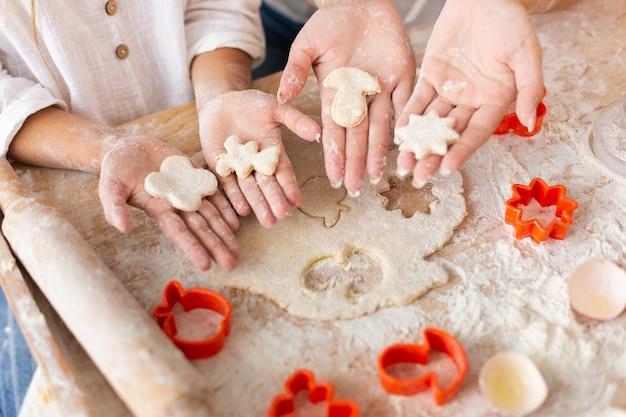 Hände, die den teig geformt in formen halten