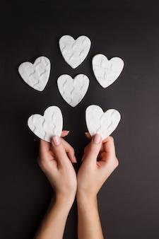 Hände, die die kleinen weißen herzen gemacht vom tonwarenlehm zeigen.