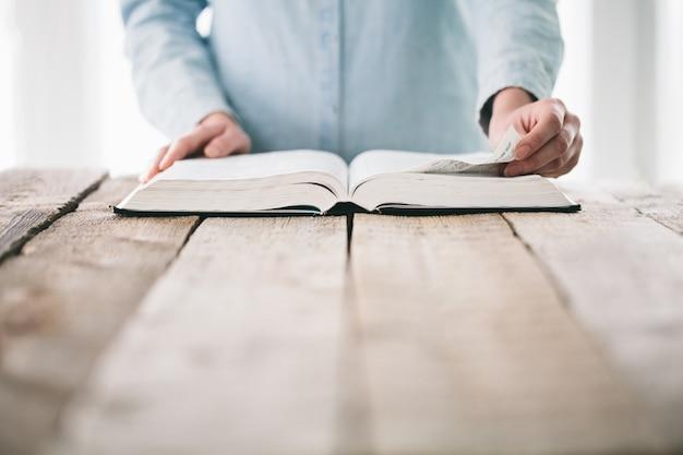 Hände, die die seite einer bibel drehen