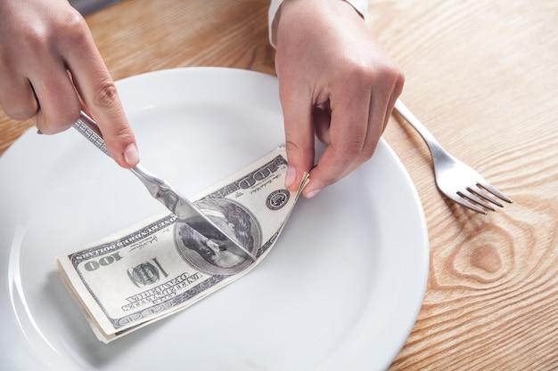 Hände, die dollarbanknote auf dem teller schneiden.