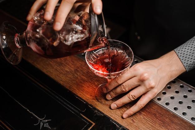 Hände, die ein frisches alkoholisches getränk in das cocktailglas umfüllen