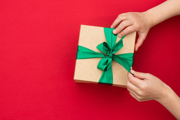 Hände, die ein geschenk in bastelpapier mit einem grünen band auf rot geben oder empfangen. draufsicht.