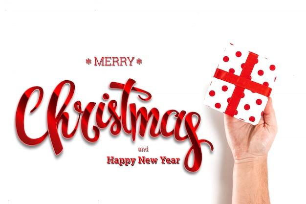 Hände, die ein geschenk und aufschrift frohen weihnachten auf einem weiß halten. weihnachtskarte, festlicher hintergrund. gemischte medien.