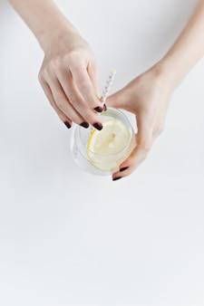 Hände, die ein glas klares wasser mit zitrone halten.