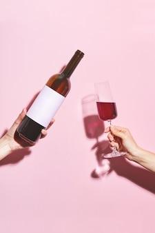 Hände, die ein glas wein und eine flasche auf rosa hintergrund halten