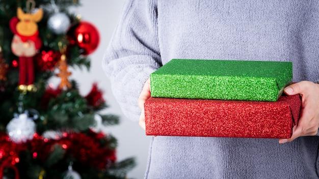 Hände, die ein grünes und rotes funkelnpackpapier weihnachtsgeschenk halten