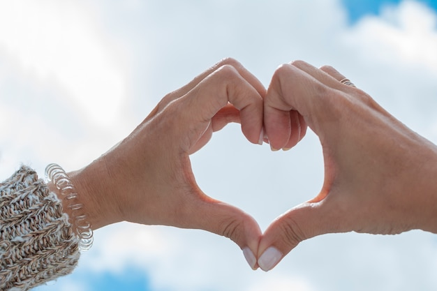 Hände, die ein herz in richtung zum himmel bilden