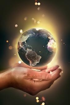 Hände, die ein leuchtendes erdkonzept des erdtages halten, das energie spart, um die umwelt zu schützen...