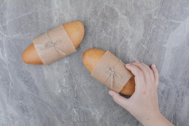 Hände, die ein minibrot auf marmoroberfläche halten