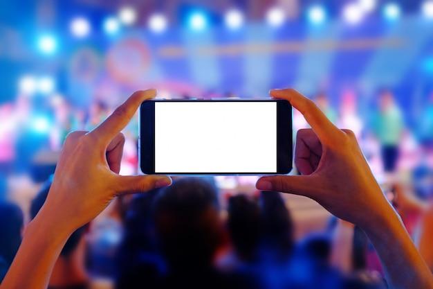 Hände, die ein mobiltelefon halten, zeichnen buntes live-konzert mit leerem weißen bildschirm auf.