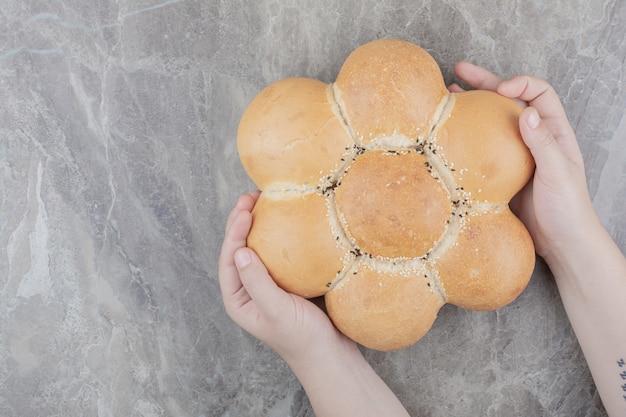 Hände, die ein rundes brot auf marmoroberfläche halten