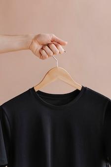 Hände, die ein schwarzes t-shirt in einem kleiderbügel halten