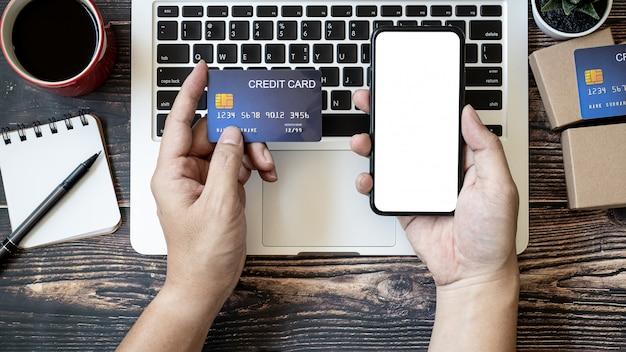 Hände, die ein smartphone und eine kreditkarte auf einem holztisch halten, um online einzukaufen