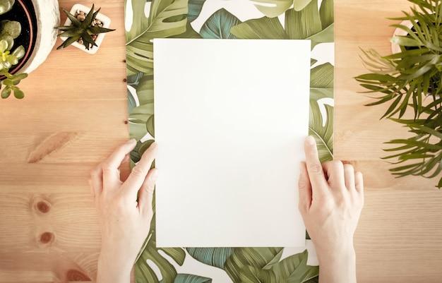 Hände, die ein weißes papier mit platz für text auf einer holzoberfläche mit grünen pflanzen berühren