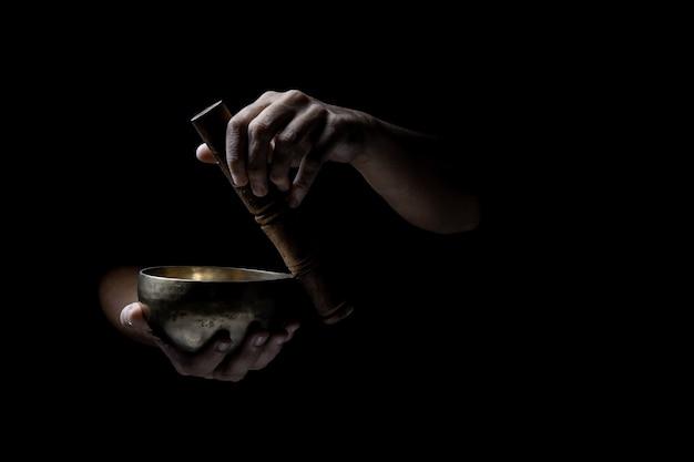Hände, die eine alte tibetanische klangschale spielen. schwarzer hintergrund. musiktherapie.