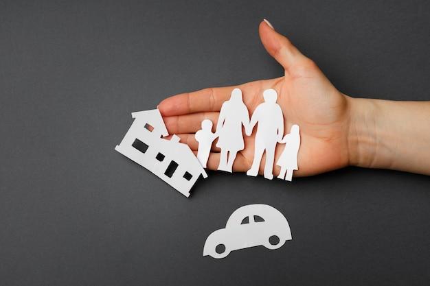 Hände, die eine familie schützen; symbol der lebensversicherung auf schwarzem hintergrund