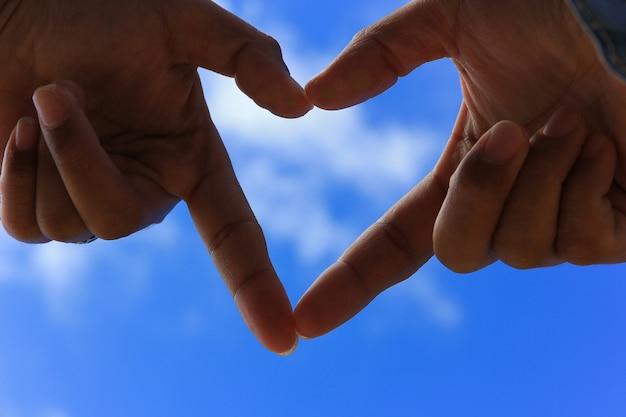 Hände, die eine herzform mit blauem himmel der unschärfe machen. liebeskonzept