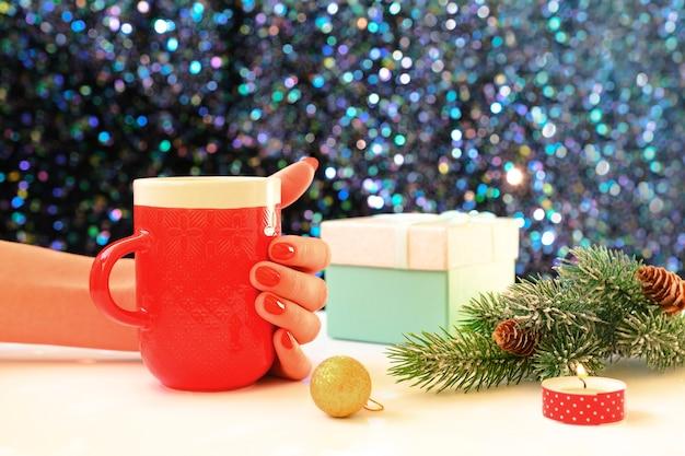 Hände, die eine kaffeetasse auf einem weihnachtshintergrund halten. sicht von oben. weibliche hände, die kaffeetasse halten. weihnachtsgeschenkboxen und schneetannenbaum über holztisch.