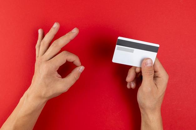 Hände, die eine kreditkarte auf rotem hintergrund halten