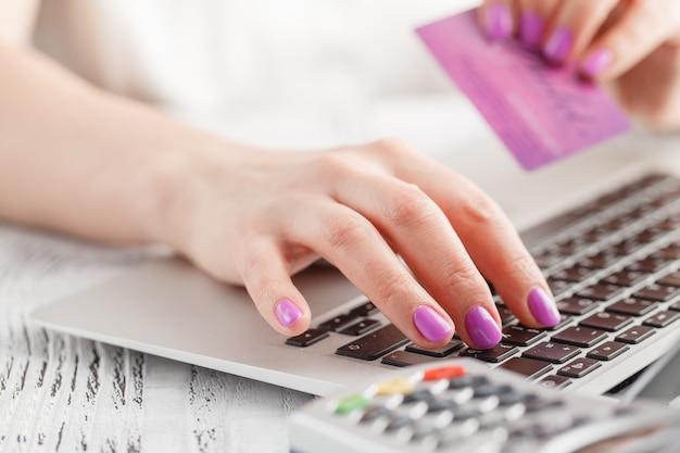 Hände, die eine kreditkarte halten und laptop für online-einkäufe verwenden