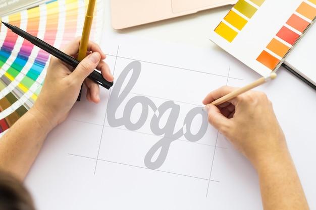 Hände, die eine logotop-ansicht zeichnen