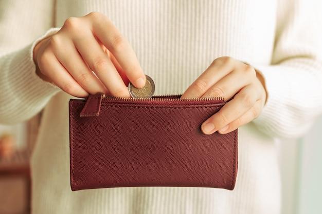 Hände, die eine münze in eine brieftasche einführen