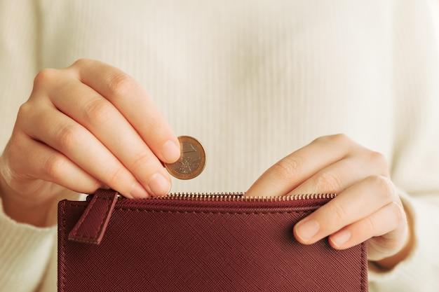 Hände, die eine münze in eine geldbörse einführen