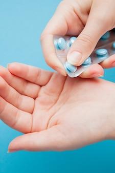 Hände, die eine packung der blauen pillen gegen einen blauen hintergrund öffnen.