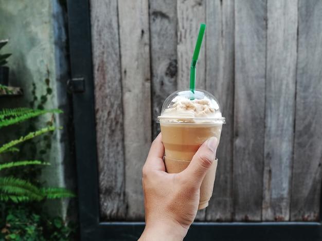 Hände, die eine schale kalten kaffee anhalten.