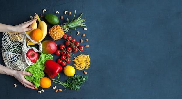 Hände, die eine schnurtasche mit gesundem vegetarischem essen halten vielfalt an gemüse und obst