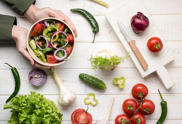 Hände, die eine schüssel mit salat arrangieren