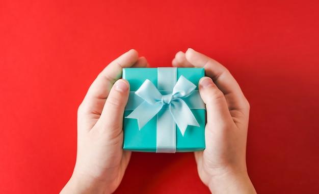 Hände, die eine türkisfarbene geschenkbox auf einer roten oberfläche halten