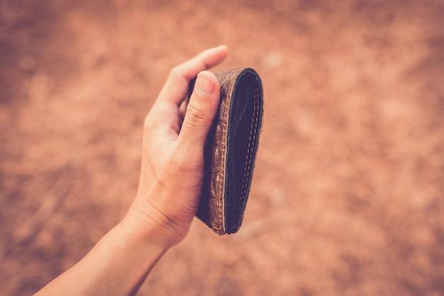 Hände, die einen geldbeutel ohne geld halten.