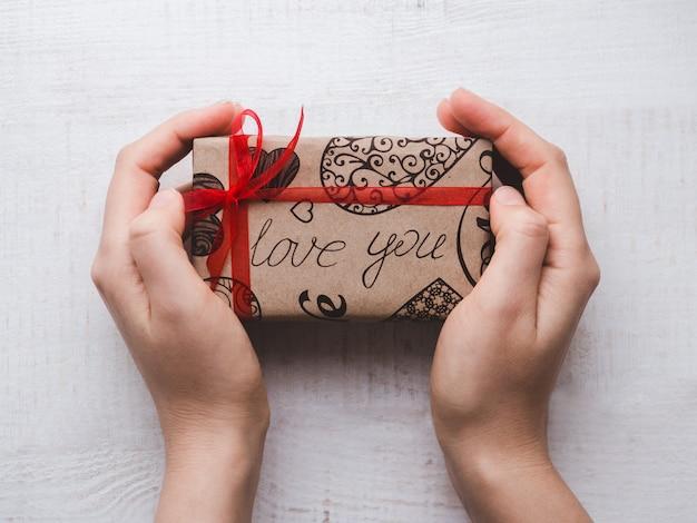 Hände, die einen kasten mit einem geschenk anhalten