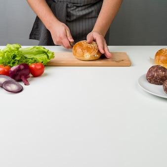 Hände, die einen köstlichen burger zubereiten