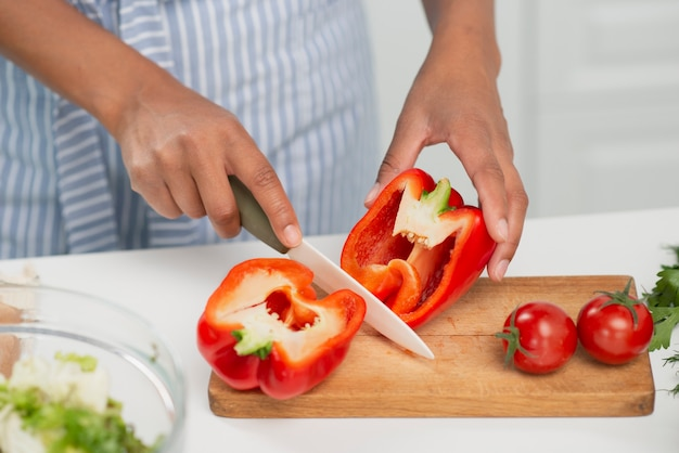 Hände, die einen köstlichen roten pfeffer schneiden