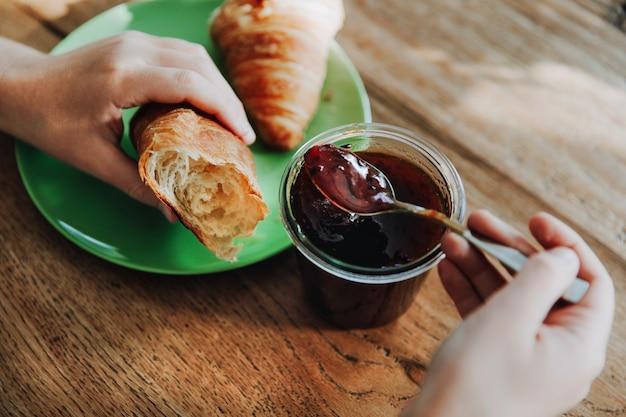 Hände, die einen löffel mit pflaumenmarmelade und ein croissant halten persönliche perspektive. einen bissen nehmen.