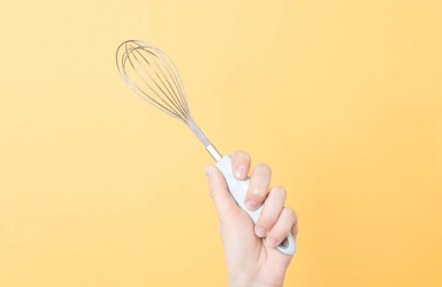 Hände, die einen metall-schneebesen auf gelbem papierhintergrund halten. küchenwerkzeug zum schlagen von sahne oder eiern.