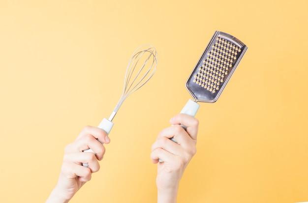 Hände, die einen metall-schneebesen und eine reibe für gemüse auf gelbem papierhintergrund halten. küchenwerkzeug zum schlagen von sahne oder eiern.