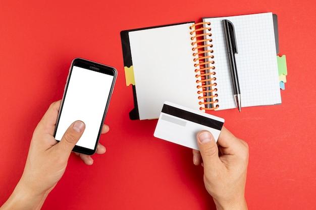 Hände, die einen notizbuch- und telefonspott hochhalten