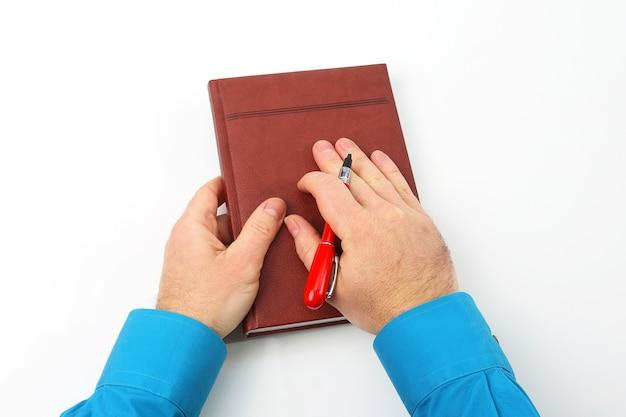 Hände, die einen roten stift und ein notizbuch auf weiß halten