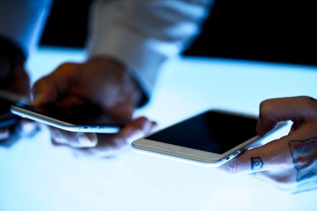 Hände, die einen smartphone unter verwendung es halten