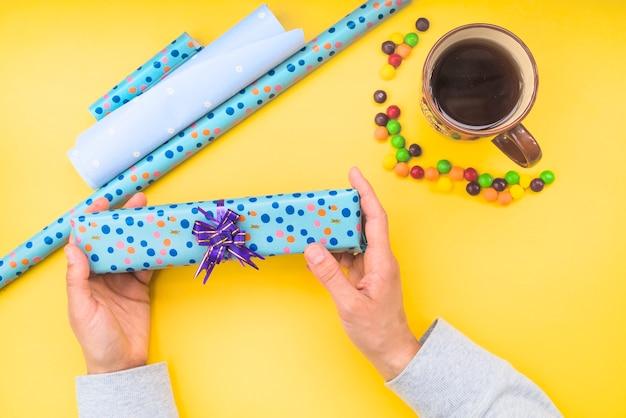 Hände, die eingewickelte geschenkbox mit süßigkeiten und kaffeetasse auf gelbem hintergrund halten