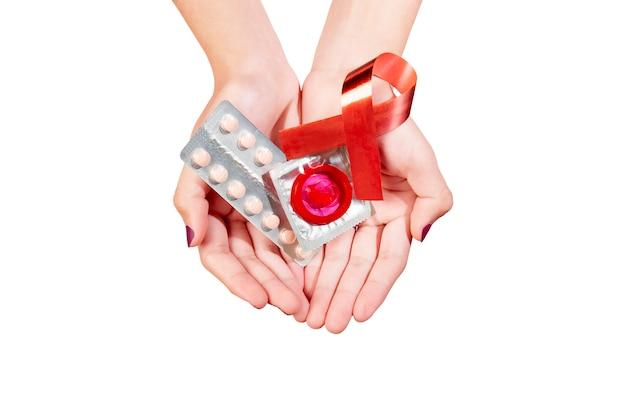 Hände, die eingewickeltes kondom und empfängnisverhütende medizin mit rotem bewusstseinsband zeigen