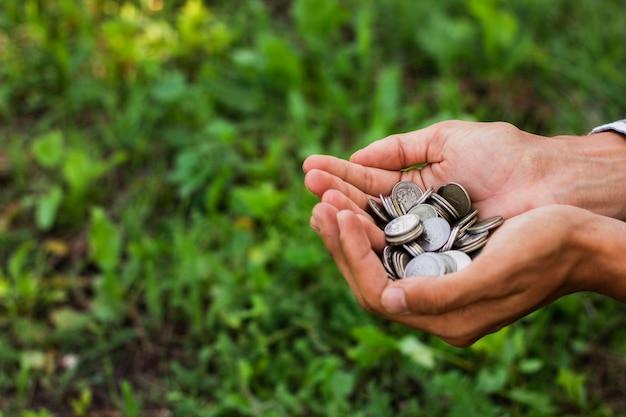 Hände, die einsparungsmünzen im freien halten